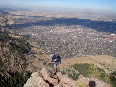 Pat walking along the top of the First Flatiron With boulder sprawling below.