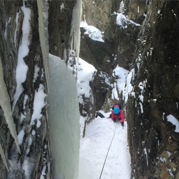 Alexa on the crux of the Cleft. Using a drop knee to surmount the chockstone